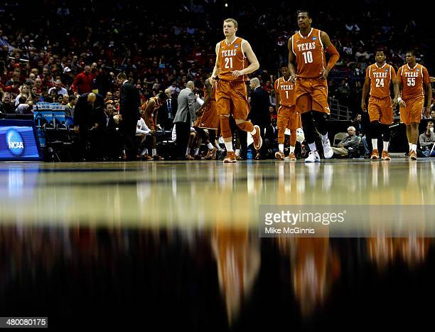 Connor Lammert and Jonathan Holmes of the Texas Longhorns walk on the court during a break in play against the Michigan Wolverines in the third round...