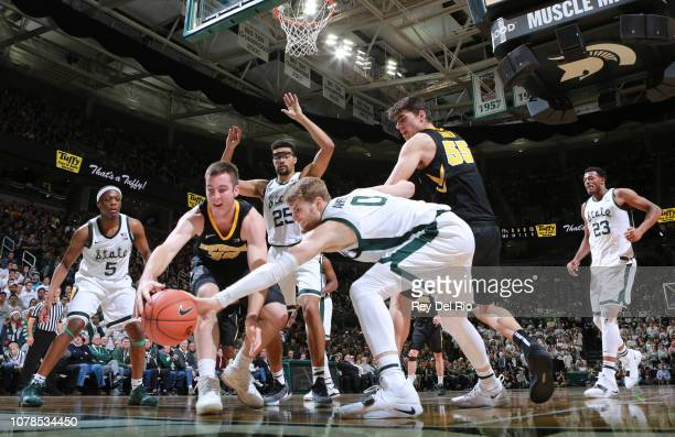 Connor McCaffery of the Iowa Hawkeyes fight for a loose ball against Kyle Ahrens of the Michigan State Spartans at Breslin Center on December 3 2018...