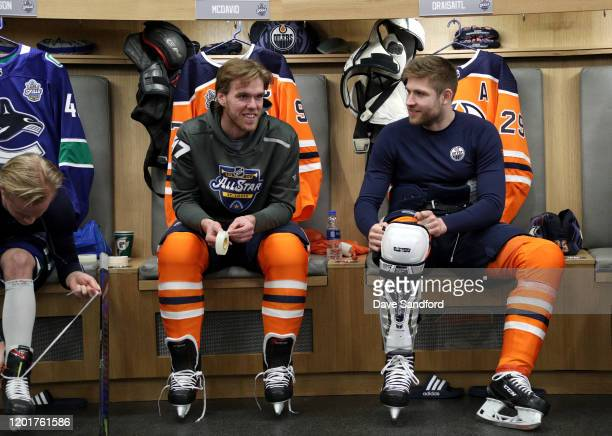 Connor McDavid and Leon Draisaitl of the Edmonton Oilers get ready in their locker room stalls prior to the 2020 NHL AllStar Skills competition at...