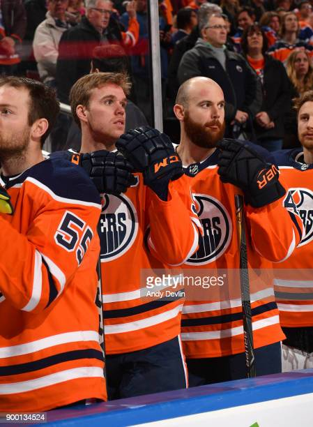 Connor McDavid and Zack Kassian of the Edmonton Oilers stand for the singing of the national anthem prior to the game against the Winnipeg Jets on...