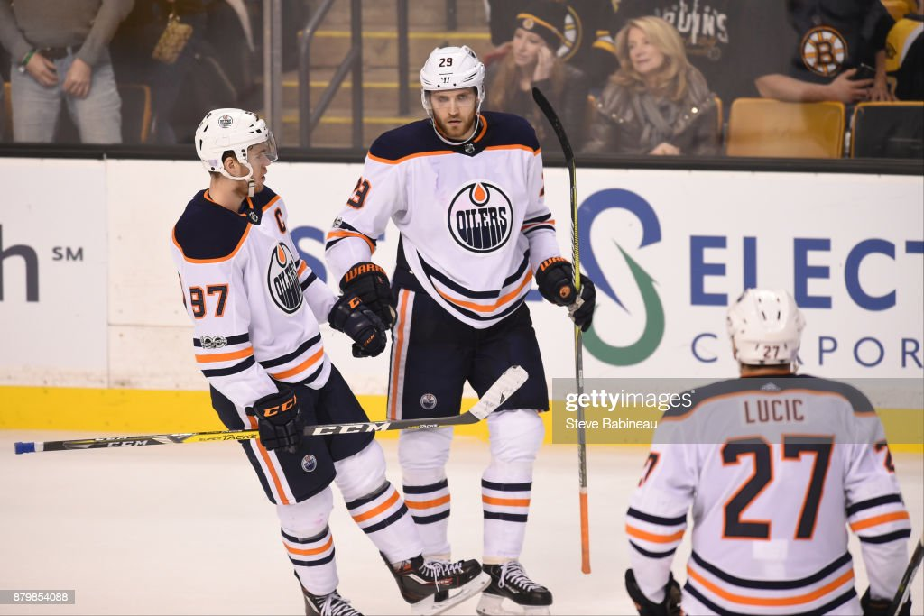 Connor McDavid #97, Leon Draisaitl #29 and Milan Lucic #27 of the Edmonton Oilers celebrate an empty net goal against the Boston Bruins at the TD Garden on November 26, 2017 in Boston, Massachusetts.