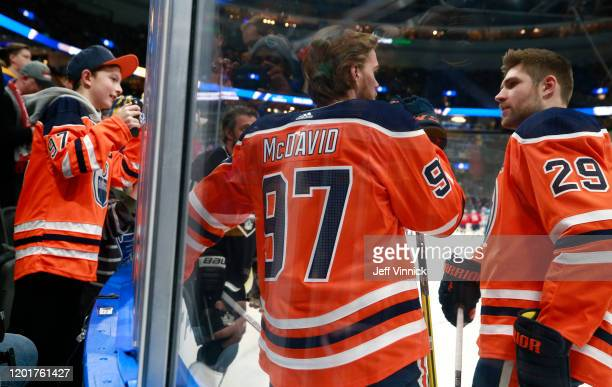 Connor McDavid Leon Draisaitl of the Edmonton Oilers talk in the corner during warmup as a fan looks on prior to the 2020 NHL AllStar Skills...