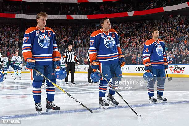 Connor McDavid Milan Lucic and Jordan Eberle of the Edmonton Oilers skates stand for the singing of the national anthem prior to the preseason game...