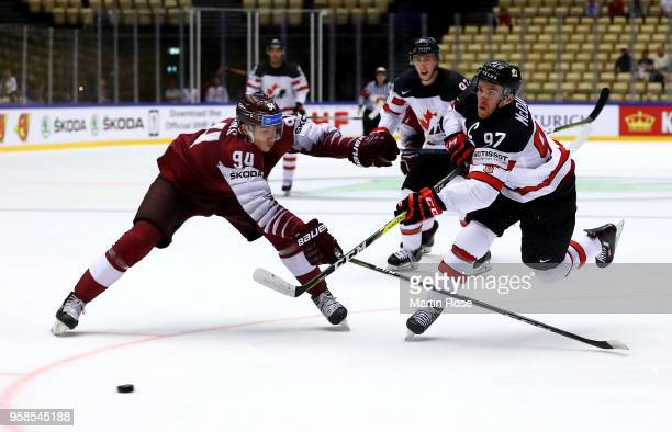 Connor McDavid of Canada and Kristians Rubins of Latvia battle for the puck during the 2018 IIHF Ice Hockey World Championship Group B game between...