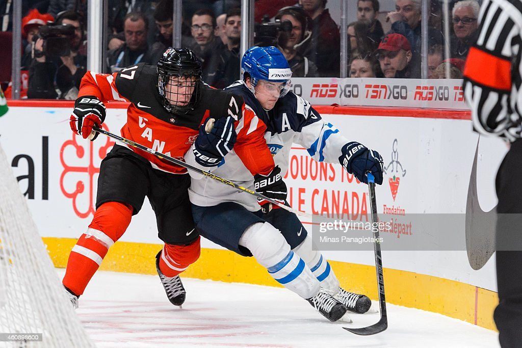 Connor McDavid #17 of Team Canada pushes Julius Honka #9 of Team Finland during the 2015 IIHF World Junior Hockey Championship game at the Bell Centre on December 29, 2014 in Montreal, Quebec, Canada. Team Canada defeated Team Finland 4-1.