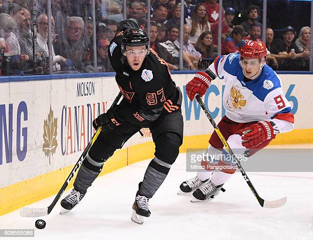 Connor McDavid of Team North America stickhandles the puck with Dmitry Orlov of Team Russia chasing during the World Cup of Hockey 2016 at Air Canada...
