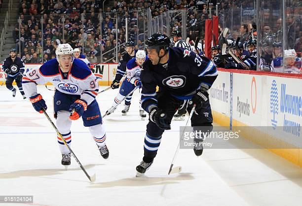 Connor McDavid of the Edmonton Oilers and Dustin Byfuglien of the Winnipeg Jets chase the play down the ice during third period action at the MTS...