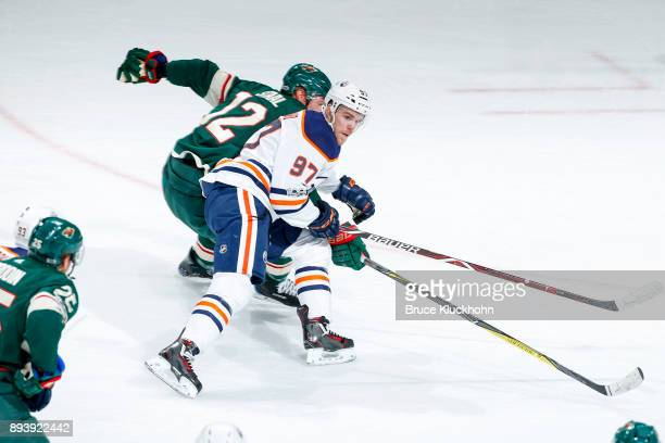 Connor McDavid of the Edmonton Oilers and Eric Staal of the Minnesota Wild skate to the puck during the game at the Xcel Energy Center on December 16...