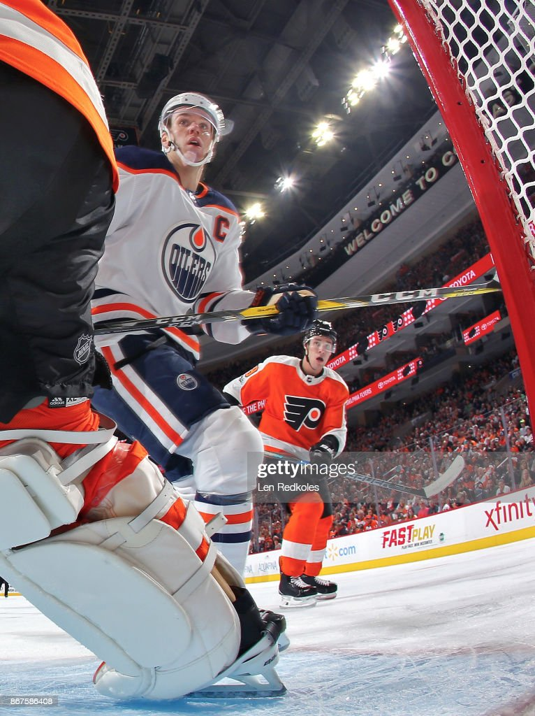 Connor McDavid #97 of the Edmonton Oilers and Ivan Provorov #9 of the Philadelphia Flyers react to the play behind the net on October 21, 2017 at the Wells Fargo Center in Philadelphia, Pennsylvania.