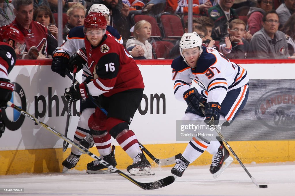 Connor McDavid #97 of the Edmonton Oilers attempts to play the puck ahead of Max Domi #16 of the Arizona Coyotes during the third period of the NHL game at Gila River Arena on January 12, 2018 in Glendale, Arizona. The Oilers defeated the Coyotes 4-2.