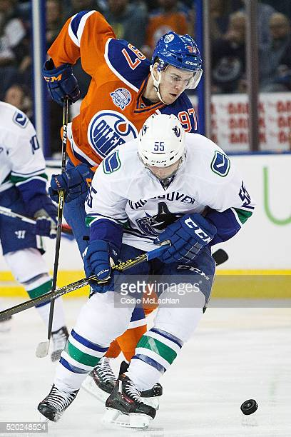 Connor McDavid of the Edmonton Oilers battles against Alex Biega of the Vancouver Canucks on April 6 2016 at Rexall Place in Edmonton Alberta Canada...