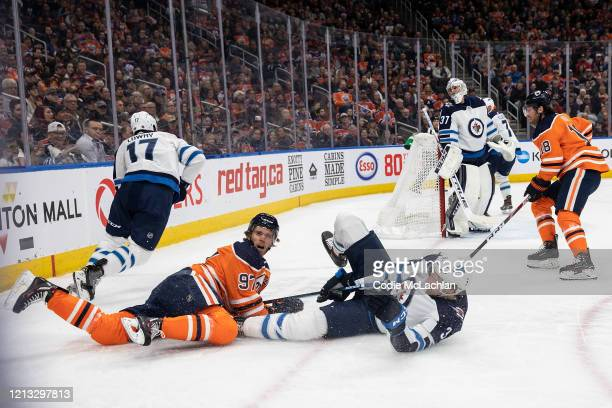 Connor McDavid of the Edmonton Oilers battles against Tucker Poolman of the Winnipeg Jets at Rogers Place on March 11 in Edmonton, Canada.