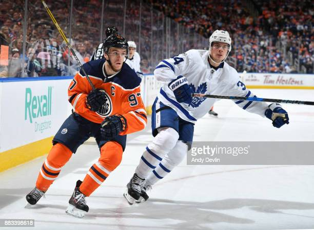 Connor McDavid of the Edmonton Oilers battles for the puck against Auston Matthews of the Toronto Maple Leafs on November 30 2017 at Rogers Place in...