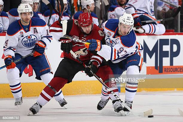 Connor McDavid of the Edmonton Oilers battles for the puck with Tobias Rieder of the Arizona Coyotes during the third period of the NHL game at Gila...