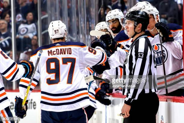 Connor McDavid of the Edmonton Oilers celebrates a first period goal against the Winnipeg Jets with teammates at the bench at the Bell MTS Place on...