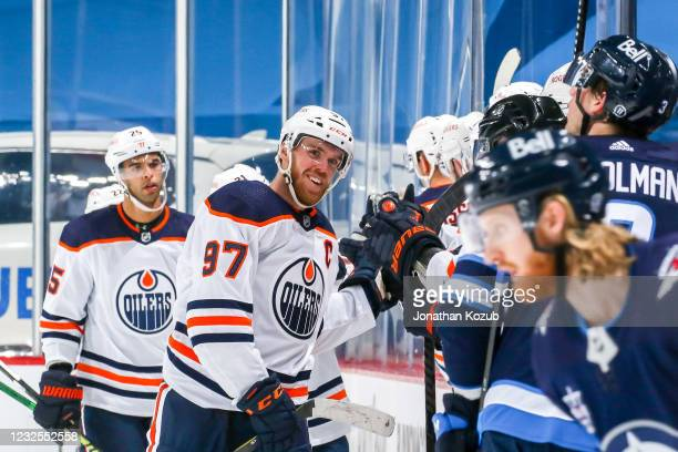 Connor McDavid of the Edmonton Oilers celebrates a second period goal against the Winnipeg Jets with teammates at the bench at the Bell MTS Place on...
