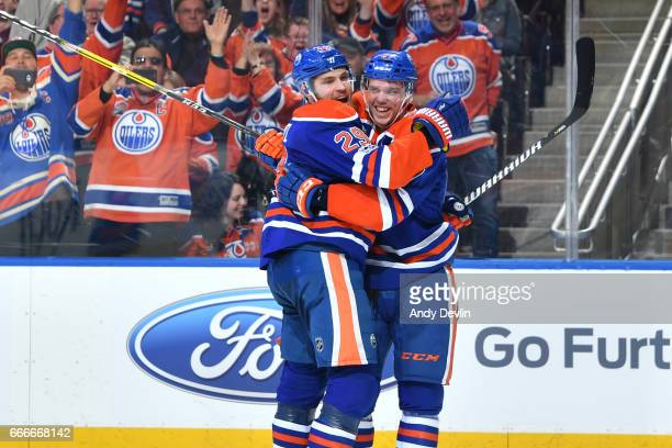 Connor McDavid of the Edmonton Oilers celebrates his 100th point of the season with Leon Draisaitl during the game against the Vancouver Canucks on...