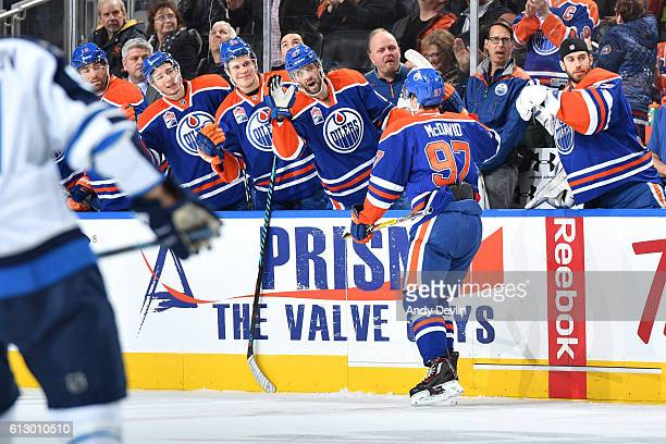 Connor McDavid of the Edmonton Oilers celebrates with team mates after scoring a goal during a preseason game against the Winnipeg Jets on October 6...