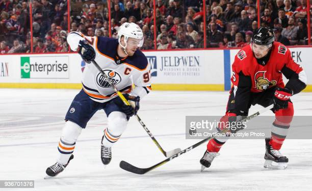 Connor McDavid of the Edmonton Oilers chips the puck past Cody Ceci of the Ottawa Senators in the first period at Canadian Tire Centre on March 22...