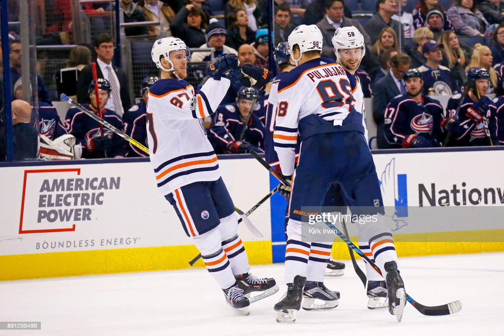 Connor McDavid #97 of the Edmonton Oilers congratulates Jesse Puljujarvi #98 of the Edmonton Oilers after scoring a goal during the third period of the game against the Columbus Blue Jackets on December 12, 2017 at Nationwide Arena in Columbus, Ohio. Edmonton defeated Columbus 7-2.