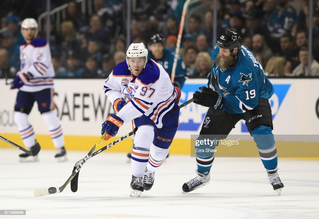 Connor McDavid #97 of the Edmonton Oilers controls the puck in front of Joe Thornton #19 of the San Jose Sharks on his way to scoring an empty net goal at the end of the third period of Game Six of the Western Conference First Round during the 2017 NHL Stanley Cup Playoffs at SAP Center on April 22, 2017 in San Jose, California.
