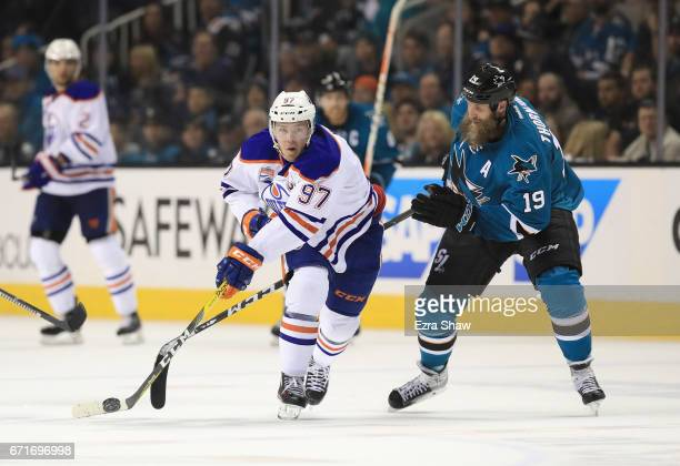 Connor McDavid of the Edmonton Oilers controls the puck in front of Joe Thornton of the San Jose Sharks on his way to scoring an empty net goal at...