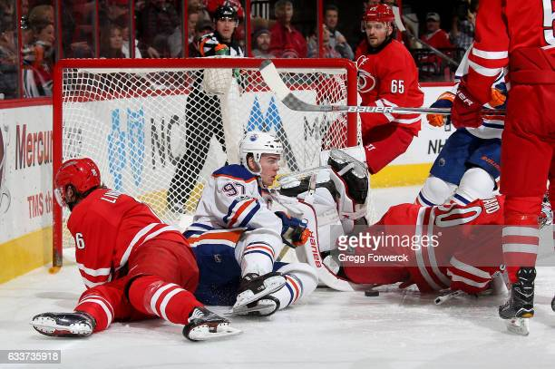 Connor McDavid of the Edmonton Oilers crashes the crease and scores knocking the net off its mooring and colliding with Cam Ward and Elias Lindholm...