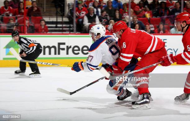 Connor McDavid of the Edmonton Oilers crashes the crease as Elias Lindholm of the Carolina Hurricanes defends during an NHL game on February 3 2017...