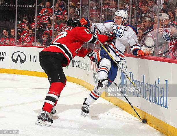 Connor McDavid of the Edmonton Oilers is checked by Ben Lovejoy of the New Jersey Devils during the third period at the Prudential Center on January...