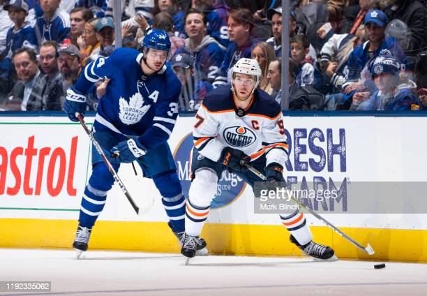 Connor McDavid of the Edmonton Oilers plays the puck against Auston Matthews of the Toronto Maple Leafs during the third period at the Scotiabank...