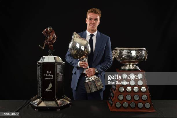 Connor McDavid of the Edmonton Oilers poses for a portrait with the Ted Lindsay Award Hart Memorial Trophy and the Art Ross Trophy at the 2017 NHL...