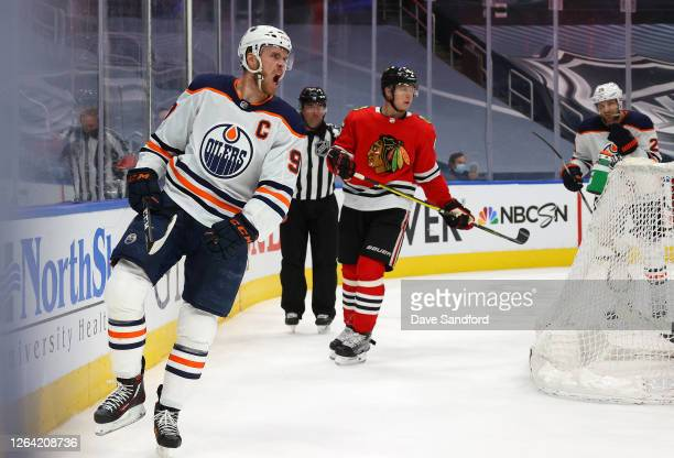 Connor McDavid of the Edmonton Oilers reacts after scoring a goal as Olli Maatta of the Chicago Blackhawks and Leon Draisaitl of the Edmonton Oilers...