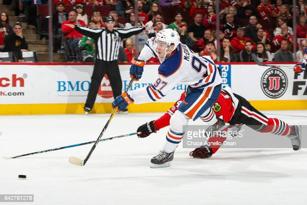 Connor McDavid of the Edmonton Oilers shoots the puck resulting in an emptynet goal against the Chicago Blackhawks in the third period at the United...
