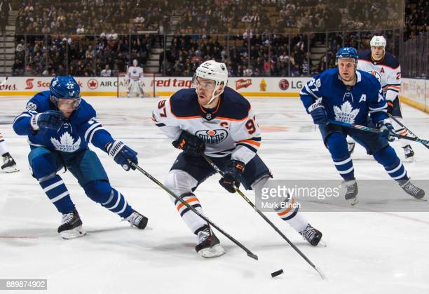 Connor McDavid of the Edmonton Oilers skates against Nikita Zaitsev and Leo Komarov of the Toronto Maple Leafs during the second period at the Air...