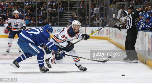Connor Mcdavid of the Edmonton Oilers skates around Nikita Zaitsev of the Toronto Maple Leafs during an NHL game at the Air Canada Centre on December...