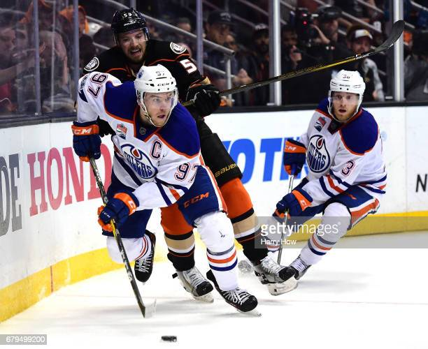 Connor McDavid of the Edmonton Oilers skates away from Shea Theodore of the Anaheim Ducks as Drake Caggiula looks on during the first overtime in...