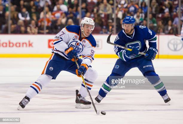 Connor McDavid of the Edmonton Oilers skates past Alex Biega of the Vancouver Canucks in NHL action on April 8 2017 at Rogers Arena in Vancouver...