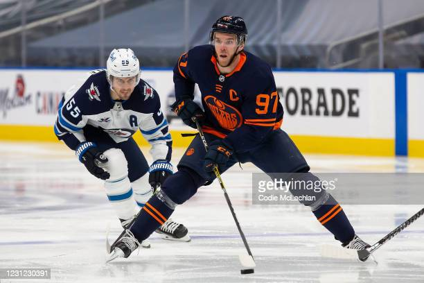 Connor McDavid of the Edmonton Oilers skates the puck against Mark Scheifele of the Winnipeg Jets at Rogers Place on February 17, 2021 in Edmonton,...