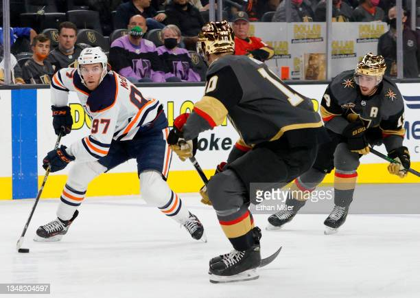 Connor McDavid of the Edmonton Oilers skates with the puck against Nicolas Roy and Reilly Smith of the Vegas Golden Knights in the third period of...