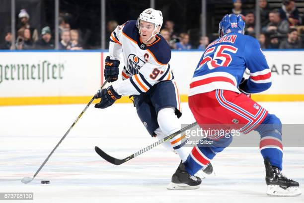 Connor McDavid of the Edmonton Oilers skates with the puck against Nick Holden of the New York Rangers at Madison Square Garden on November 11 2017...