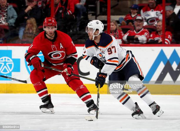 Connor McDavid of the Edmonton Oilers skates with the puck near the defense of Jordan Staal of the Carolina Hurricanes during an NHL game on March 20...