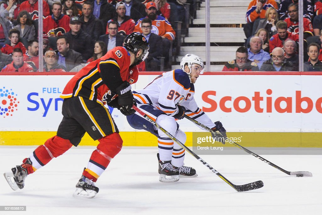 Connor McDavid #97 of the Edmonton Oilers skates with the puck past Mark Giordano #5 of the Calgary Flames during an NHL game at Scotiabank Saddledome on March 13, 2018 in Calgary, Alberta, Canada.