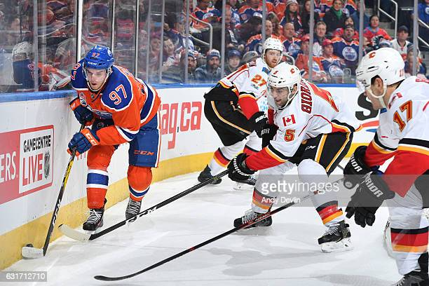 Connor McDavid of the Edmonton Oilers skates with the puck while being pursued by Mark Giordano and Lance Bouma of the Calgary Flames on January 14...
