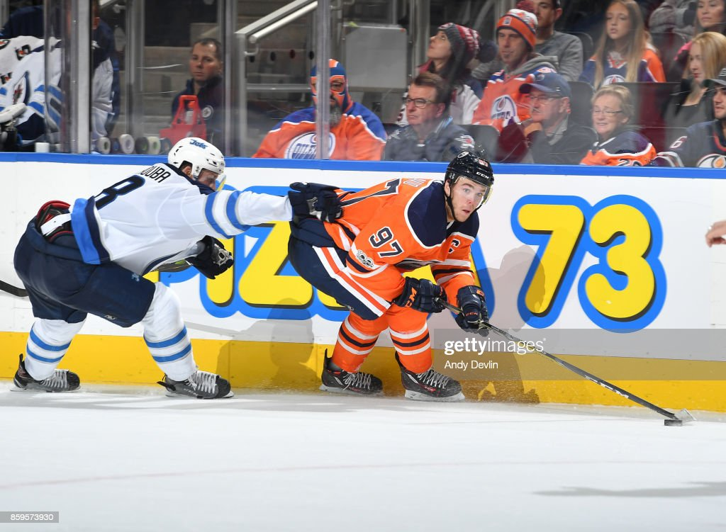 Connor McDavid #97 of the Edmonton Oilers skates with the puck while being pursued by Jacob Trouba #8 of the Winnipeg Jets on October 9, 2017 at Rogers Place in Edmonton, Alberta, Canada.