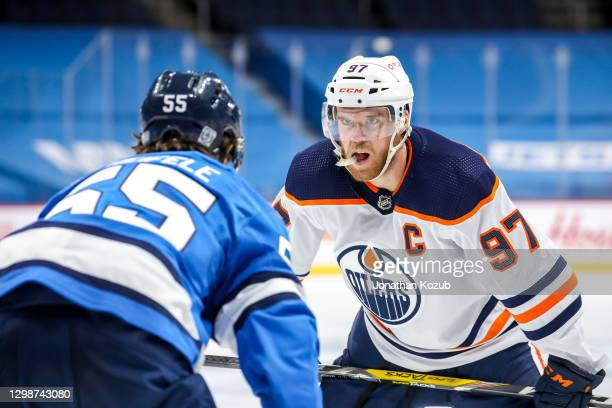 Connor McDavid of the Edmonton Oilers stares down Mark Scheifele of the Winnipeg Jets prior to a second period face-off at Bell MTS Place on January...