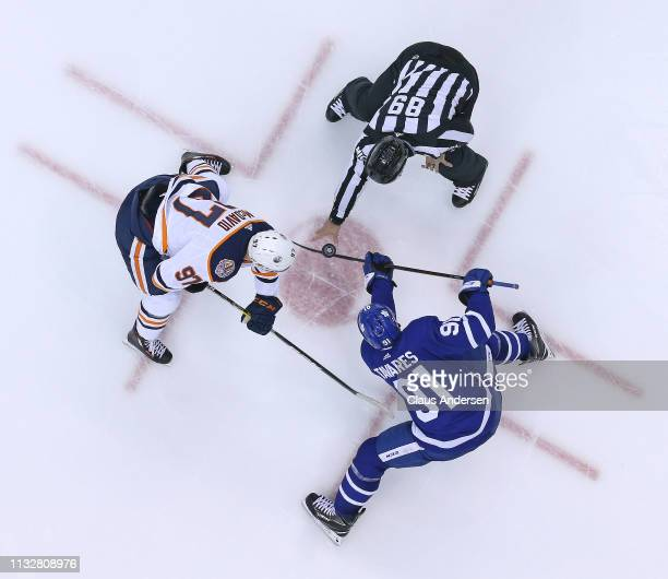 Connor McDavid of the Edmonton Oilers takes a faceoff against John Tavares of the Toronto Maple Leafs during an NHL game at Scotiabank Arena on...