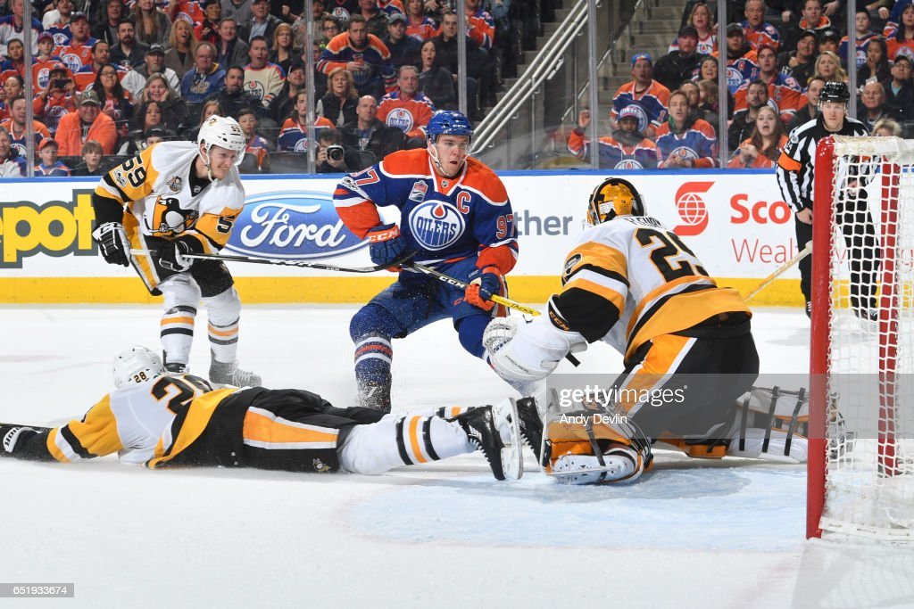 Connor McDavid #97 of the Edmonton Oilers takes a shot that is blocked by Ian Cole #28 and Marc-Andre Fleury #29 of the Pittsburgh Penguins on March 10, 2017 at Rogers Place in Edmonton, Alberta, Canada.