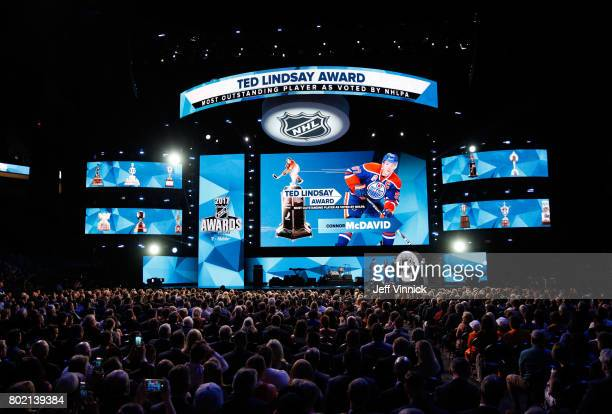 Connor McDavid of the Edmonton Oilers takes the stage as Ted Lindsay and Mark Messier look on after McDavid was awarded the Ted Lindsay Award during...