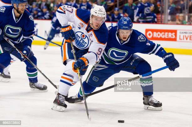 Connor McDavid of the Edmonton Oilers tries to get around Troy Stecher of the Vancouver Canucks in NHL action on April 8 2017 at Rogers Arena in...