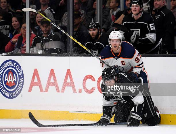 Connor McDavid of the Edmonton Oilers watches his pass leading to an empty net goal from Josh Archibald behind Drew Doughty of the Los Angeles Kings...